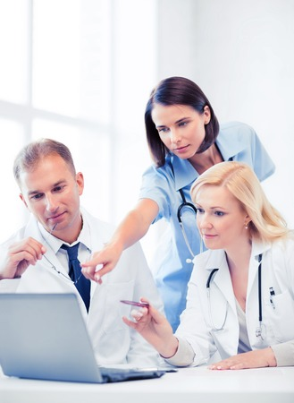 electronical: healthcare, medical and technology - group of doctors looking at laptop on meeting