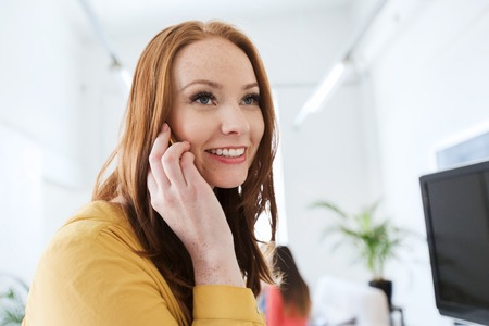 application university: business, startup and people concept - happy businesswoman or creative worker calling on smartphone at office Stock Photo