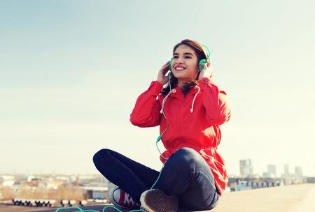listening to music: tecnología, estilo de vida y las personas concepto - mujer joven o adolescente en los auriculares escuchando música al aire libre sonriente Foto de archivo