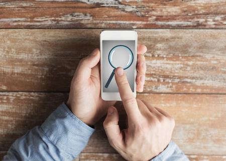 concept d'affaires, l'éducation, les gens et la technologie - gros plan des mains mâles tenant le smartphone avec loupe photo sur l'écran à la table