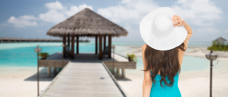 people, summer holidays, travel, tourism and vacation concept - woman in swimsuit and sun hat from back over maldives beach with bungalow background photo