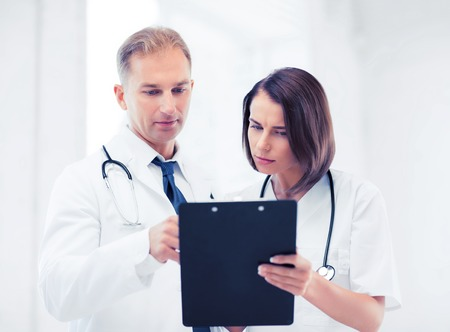 prescribing: healthcare and medical concept - two doctors discussing diagnosis Stock Photo