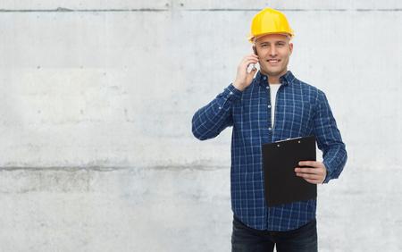 reparatie, bouw, constructie, het bedrijfsleven en het onderhoud concept - lachende man of bouwer in helm met klembord bellen op de smartphone over grijze betonnen muur achtergrond Stockfoto