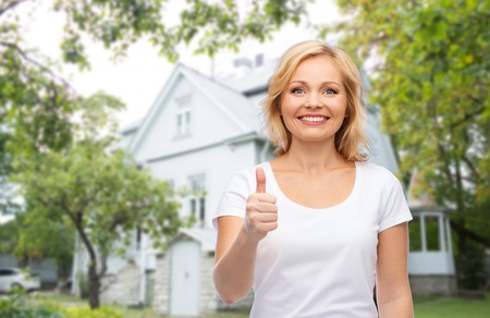 nice accommodations: gesture, advertisement, real estate, home and people concept - smiling woman in blank white t-shirt showing thumbs up over private house background