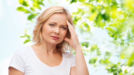 unhappy people: people, healthcare, stress and problem concept - unhappy woman suffering from headache over green natural background
