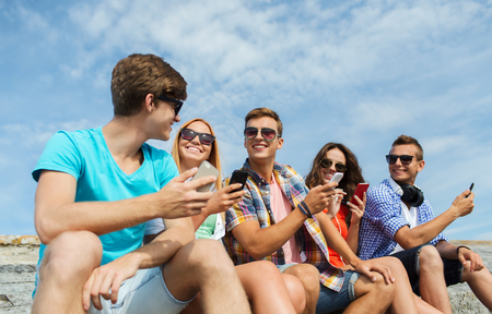 friendship, leisure, summer, technology and people concept - group of happy friends with smartphones outdoors Stock Photo