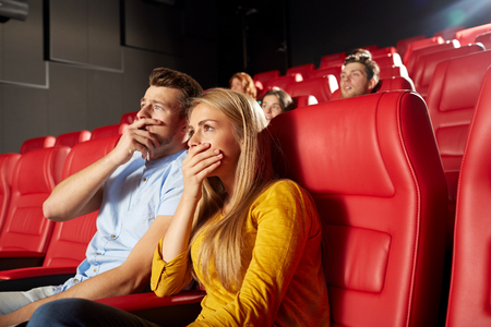 cinema, entertainment and people concept - happy friends watching horror, drama or thriller movie in theater