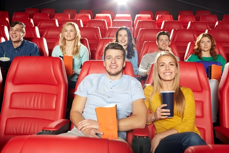 young friends: cinema, entertainment and people concept - happy friends watching movie in theater