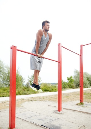 fitness, sport, training and lifestyle concept - young man exercising on horizontal bar outdoors