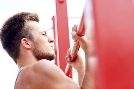 Fitness, Sport, Sport treiben, Ausbildung und Lifestyle-Konzept - junger Mann tun Pull-ups auf horizontalen Balken im Freien