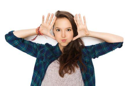 人々 および十代の若者たちのコンセプト - 幸せの笑みを浮かべてかなり 10 代の少女は顔を作ると楽しい時を過す