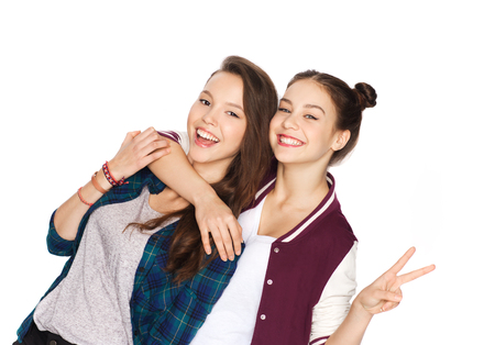 people, friends, teens and friendship concept - happy smiling pretty teenage girls hugging and showing peace hand sign