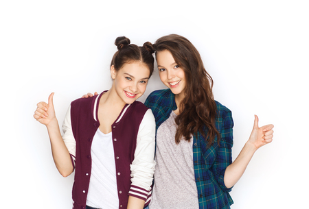 people, friends, teens and friendship concept - happy smiling pretty teenage girls hugging and showing thumbs up Stock Photo