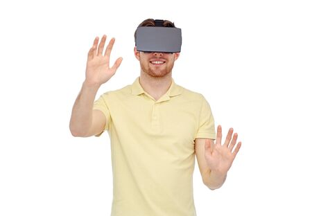 mediated: 3d technology, virtual reality, entertainment and people concept - happy young man with virtual reality headset or 3d glasses playing game Stock Photo