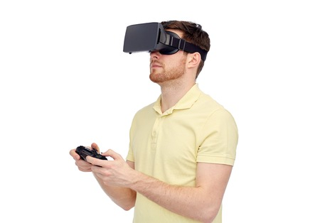 mediated: 3d technology, virtual reality, entertainment and people concept - happy young man with virtual reality headset or 3d glasses playing with game controller gamepad
