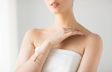 wristlet: glamour, beauty, jewelry and luxury concept - close up of beautiful woman with golden ring and bracelet
