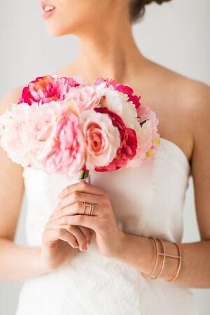 wristlet: wedding, holidays, beauty, jewelry and luxury concept - close up of beautiful woman or bride with flower bouquet wearing golden ring and bracelet
