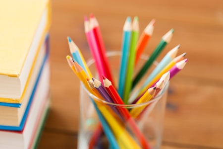 color pencils: education, art, drawing, creativity and object concept - close up of crayons or color pencils and books on wooden table