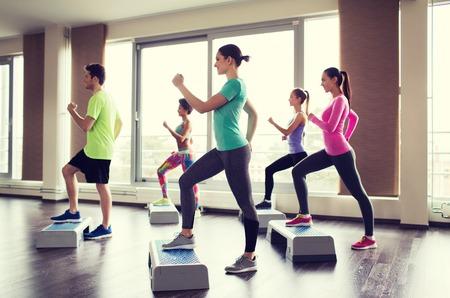 gimnasia aerobica: fitness, deporte, entrenamiento, aeróbic y concepto de la gente - grupo de personas que trabajan con motores paso a paso en el gimnasio Foto de archivo