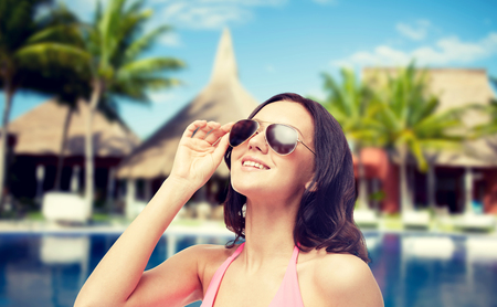 sun beach: people, summer holidays, travel and tourism concept - happy young woman in sunglasses and pink swimsuit looking up over hotel resort with swimming pool, bungalow and palm trees background Stock Photo