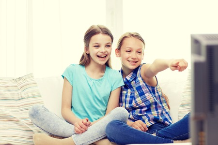 telly: people, children, television, friends and friendship concept - two happy little girls watching tv and pointing finger at home