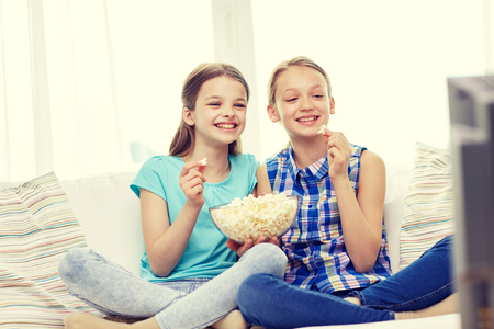 teenagers having fun: people, children, television, friends and friendship concept - two happy little girls watching comedy movie on tv and eating popcorn at home Stock Photo