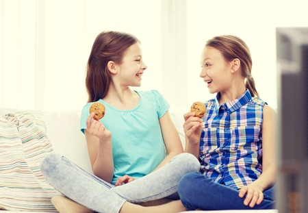 friends eating: people, children, television, friends and friendship concept - two happy little girls watching tv and eating cookies at home