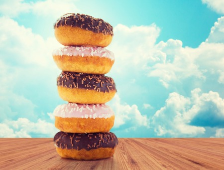 junkfood: food, junk-food and eating concept - close up of glazed donuts pile on wooden table over blue sky and clouds background Stock Photo