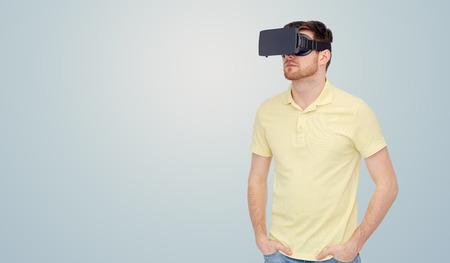 percepción: La tecnología 3D, realidad virtual, el entretenimiento y la gente concepto - joven con casco de realidad virtual o gafas 3D sobre fondo gris Foto de archivo