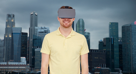mediated: 3d technology, virtual reality, travel, entertainment and people concept - happy young man with virtual reality headset or 3d glasses over singapore city skyscrapers background