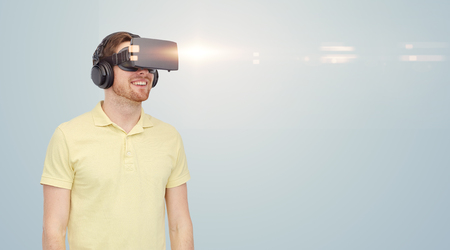 entertainment background: 3d technology, virtual reality, entertainment and people concept - happy young man with virtual reality headset or 3d glasses over gray background Stock Photo
