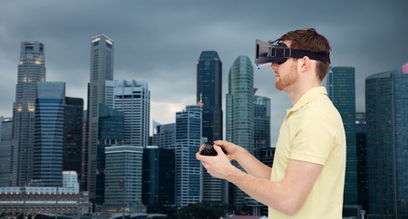 entertainment background: 3d technology, virtual reality, travel, entertainment and people concept - happy young man with virtual reality headset playing with game controller gamepad over singapore city background Stock Photo