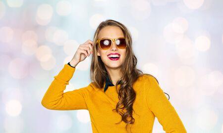 mensen, stijl en mode concept - gelukkige jonge vrouw of tiener meisje in casual kleding en een zonnebril op vakantie lichten achtergrond