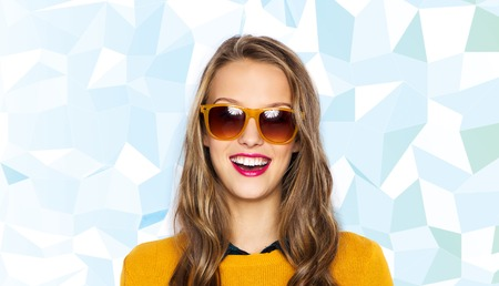 fashion background: people, style and fashion concept - happy young woman or teen girl face in sunglasses over low poly blue background