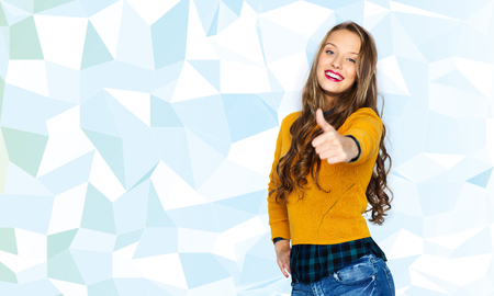 people, gesture, style and fashion concept - happy young woman or teen girl in casual clothes showing thumbs up over low poly blue background Stock Photo