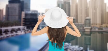 people, summer holidays, travel, tourism and vacation concept - woman in swimsuit and sun hat from back over dubai city background photo