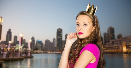 people, holidays and fashion concept - young woman or teen girl in pink dress and princess crown over evening city waterfront background Stock Photo