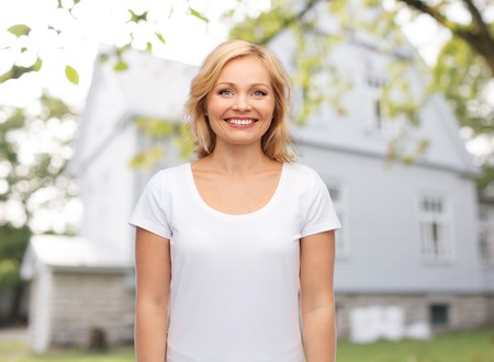 real estate, home and people concept - smiling woman in blank white t-shirt over private house background