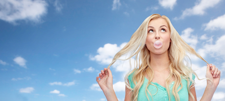 chewing gum: emotions, expressions and people concept - happy young woman or teenage girl chewing gum over blue sky and clouds background Stock Photo