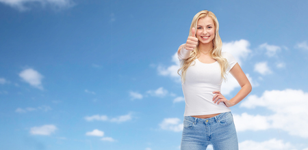 fashion clothing: emotions, expressions, advertisement and people concept - happy smiling young woman or teenage girl in white t-shirt showing thumbs up over blue sky and clouds background Stock Photo