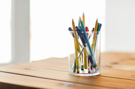 writing desk: education, office supply, writing tools and object concept - close up of stand or glass with pens and pencils on wooden table