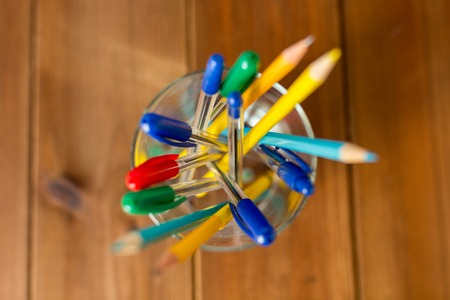 education, office supply, writing tools and object concept - close up of stand or glass with pens and pencils on wooden table