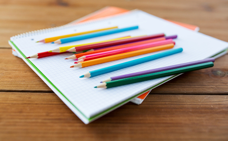 color pencils: art, school, education, drawing and object concept - close up of crayons or color pencils on notebook paper
