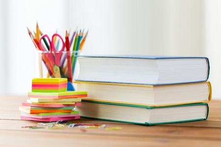 office supplies: education, school supplies, and object concept - close up of stand or glass with writing tools and book with scissors on wooden table