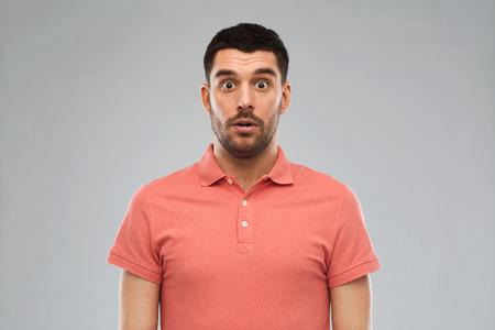 sorprendido: la emoción, la publicidad y la gente concepto - hombre sorprendido en la camiseta del polo sobre fondo gris Foto de archivo
