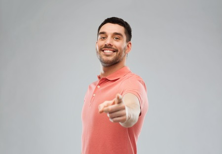 gesture and people concept - happy smiling young man pointing finger to you over gray background