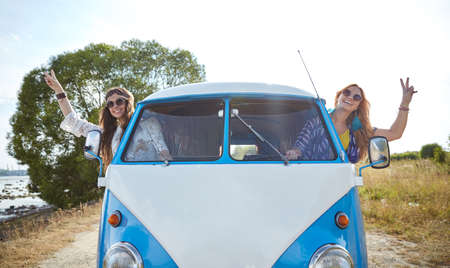 minivan: summer holidays, road trip, vacation, travel and people concept - smiling young hippie women driving minivan car and showing peace gesture