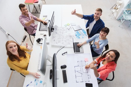 people on computers: business, startup, success and people concept - creative team with computers, blueprint and scheme showing thumbs up at office