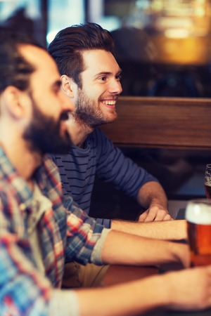 pubs: people, men, leisure, friendship and communication concept - happy male friends drinking beer at bar or pub