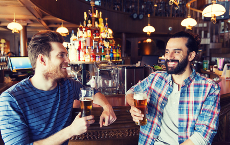 beerhouse: people, leisure, friendship, communication and bachelor party concept - happy male friends drinking beer and talking at bar or pub